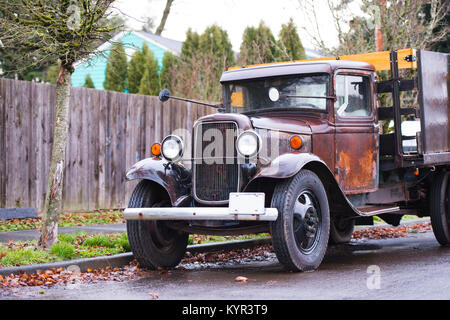 An old rarity rusty truck in working condition with a vintage design stands on the street under a fence in rainy - Stock Photo