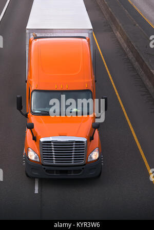 Orange semi truck with chrome grille and high roof move on the road with dry van trailer carry commercial goods - Stock Photo