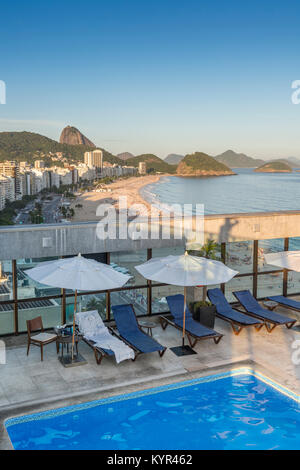 Luxurious aerial view of Copacabana beach from a rooftop swimming pool lounge area - concept of literally living - Stock Photo