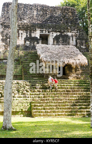 TIKAL, GUATEMALA - NOVEMBER 26: Unidentified people climbed mayan temple ruins at an archealogical site in Tikal - Stock Photo