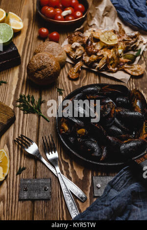 Assorted cooked seafood with bread and tomatoes on wooden table - Stock Photo