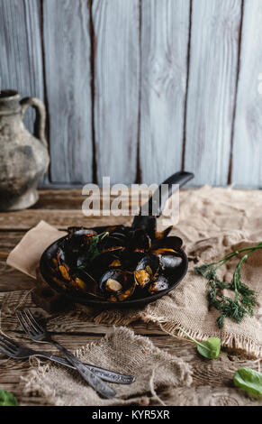 gourmet fried mussels with shells on frying pan and forks on table - Stock Photo