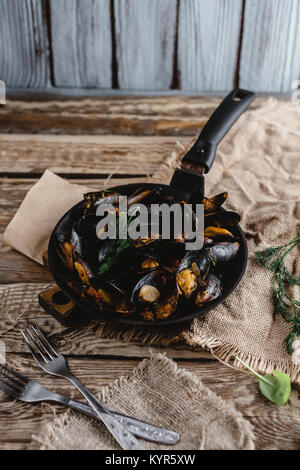 close-up view of delicious fried mussels with shells on frying pan and forks on table - Stock Photo