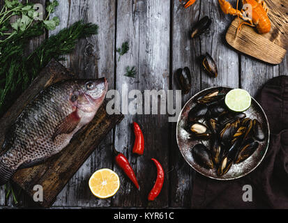 top view of raw fish on cutting board and mussels with lime on rustic wooden table - Stock Photo