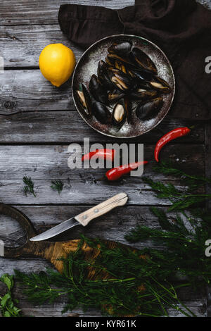 top view of delicious mussels with shells on vintage plate with herbs, chili peppers and lemon on rustic wooden - Stock Photo
