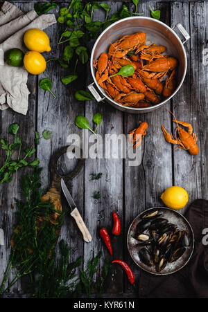 top view of lobsters and mussels in pans and citrus fruits with herbs on rustic wooden table - Stock Photo