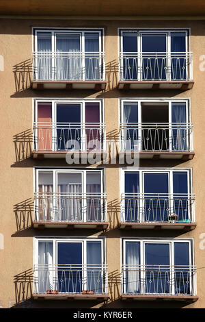 The railings of small balconies of an apartment building cast shadows. - Stock Photo