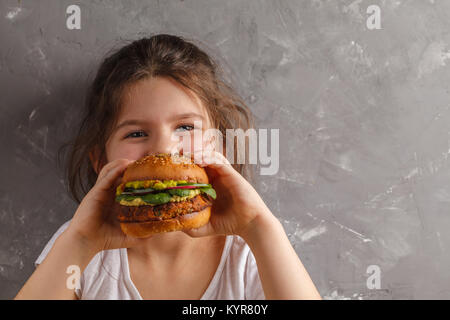 The little girl is eating a healthy baked sweet potato burger with a whole grains bun, guacamole, vegan mayonnaise - Stock Photo