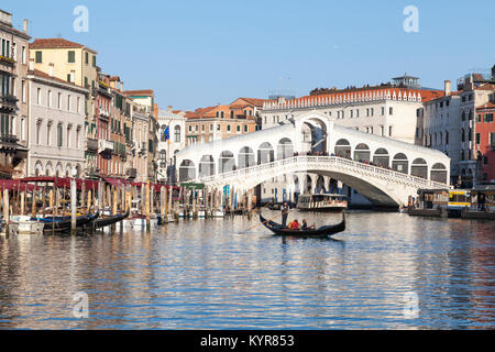 Rialto, Venice. Gondola on the Grand Canal in front of the Rialto Bridge, Venice, Veneto, Italy with reflections. - Stock Photo