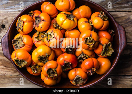 Pot of fresh fruits persimmon kaki on old wooden background. Copy space - Stock Photo