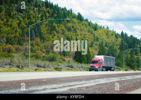 Red big rig modern shiny semi-truck with black tarp dry van trailer with aerodynamic spoiler in front of trailer - Stock Photo