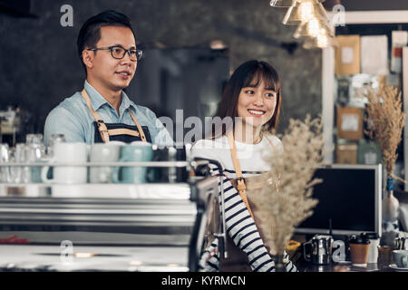 Asia Barista waiter smile and talking to customer in coffee shop,Two cafe owner at counter bar,Food and drink business - Stock Photo