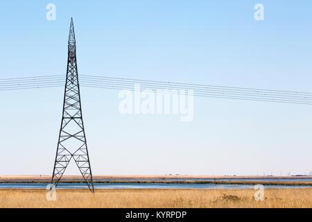 Transmission tower along prairie lake - Stock Photo