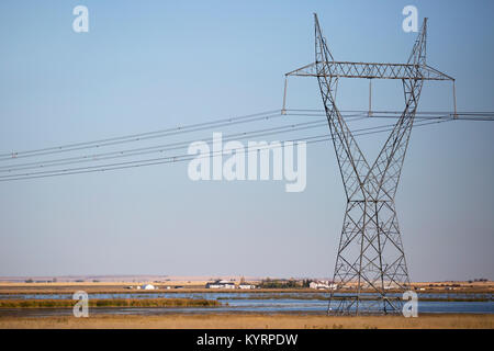 Transmission tower across prairie lake - Stock Photo