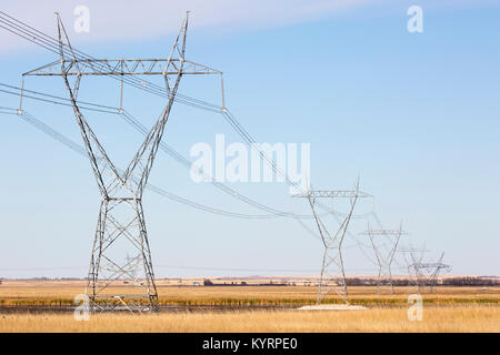 Transmission towers across prairie lake - Stock Photo