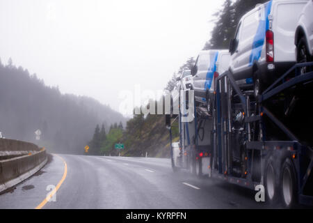 A powerful car hauler semi truck transporting cars on a special two-level trailer along the winding highway in the - Stock Photo