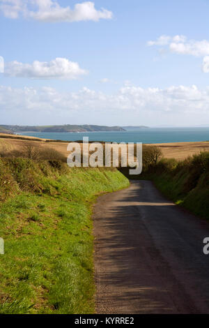 An empty country road winding down towards coast, Pembrokeshire, Wales, UK - Stock Photo