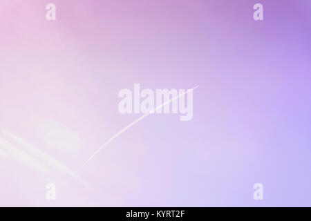 Bright clear blue sky with diagonal jet plane trace, track, condensation vapor trails toned fashionable ultraviolet - Stock Photo