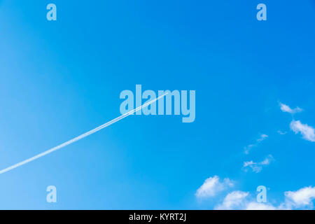 Bright clear blue sky background with diagonal jet plane trace, track, Airplane trace, condensation trails, vapor - Stock Photo