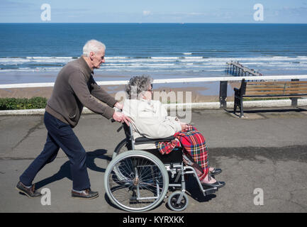 Elderly man pushing edlerly woman in wheelchair on seafront. UK - Stock Photo