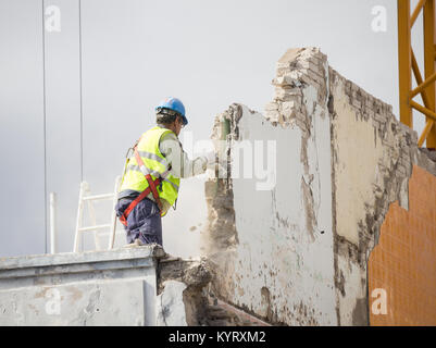 Workman demolishing wall on high building without safety harness being attached. - Stock Photo