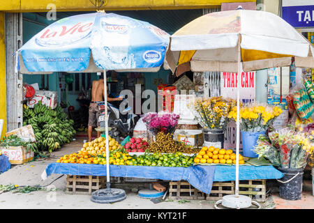 Street view in Saigon (Ho Chi Minh City), south Vietnam: typical colourful roadside fresh fruit, produce and flower - Stock Photo