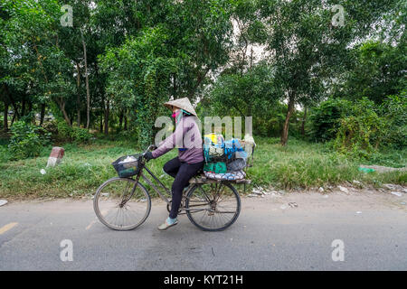 Street view in rural Saigon (Ho Chi Minh City), south Vietnam: local Vietnamese woman wearing a coolie hat riding - Stock Photo