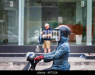 Female motorcyclist wearing an unsafe crash helmet incorrectly over a hat and a hood: street scene in Saigon (Ho - Stock Photo