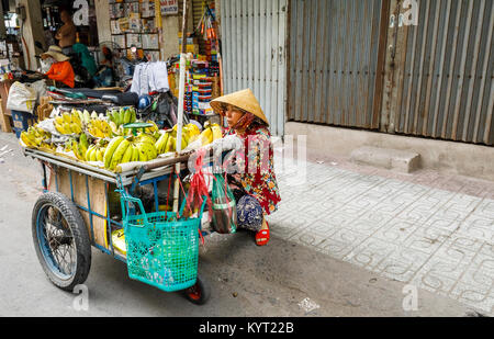 Local woman wearing a coolie hat selling bananas on the roadside from a barrow: street view in suburban Saigon (Ho - Stock Photo