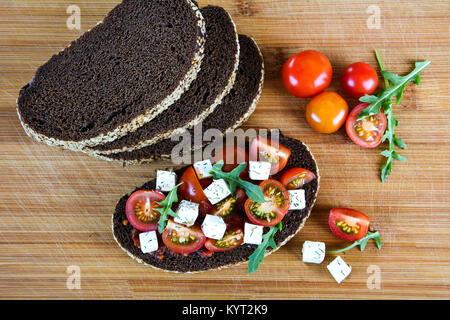 Juicy sandwich with tomato, cheese and herbs on black bread with cereals background - Stock Photo