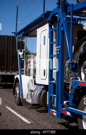 A classic simple powerful bright white big rig semi truck with a two-tier car hauler trailer for the transport of - Stock Photo