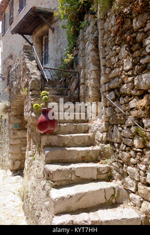 Steps leading to the entrance of an ancient building folded in the past from natural rough stones in the old village - Stock Photo