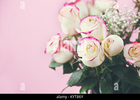 Beautiful bouquet of  red and white roses with baby's breath against a pink background. Selective focus on roses - Stock Photo