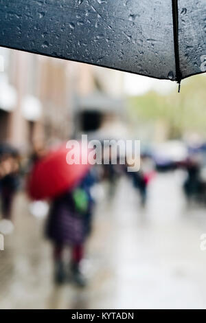 closeup of a wet umbrella and some blurred people walking under the rain protected by umbrellas in a street of a - Stock Photo