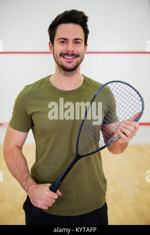 Portrait of male squash player with racket on court - Stock Photo
