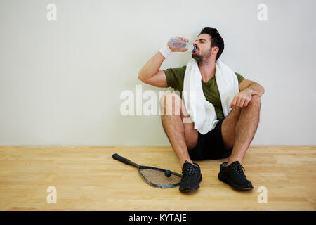 Male squash player drinking water - Stock Photo