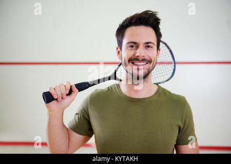 Front view of man with racket before squash game - Stock Photo