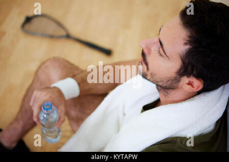 Man resting after practice at squash - Stock Photo