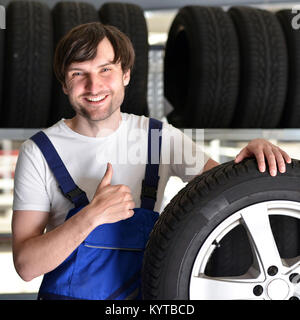 workers in a warehouse with tyres for changing the car - Stock Photo