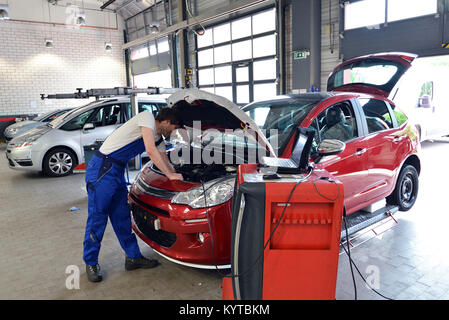 mechanic repairs motor from an automobile with the help of a diagnostic computer - Stock Photo