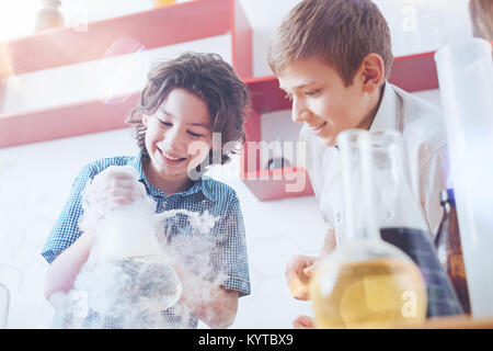 Future scientists. Happy boys standing in the laboratory and holding a fuming vacuum flask while working on a school - Stock Photo