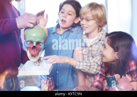 Rising curiosity. Smart experienced nice professor giving a lecture on human anatomy while using special plastic - Stock Photo