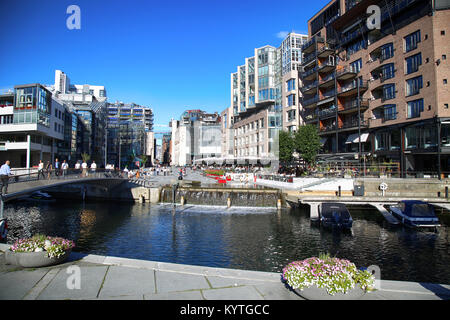 OSLO, NORWAY – AUGUST 17, 2016: People walking on wonderful modern residential district Aker Brygge with lux apartments, - Stock Photo