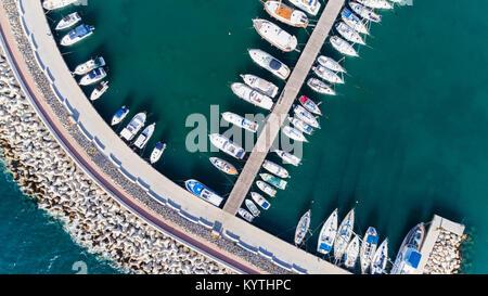 Aerial bird's eye view of Zygi fishing village port, Larnaca, Cyprus. Bird eye view of aligned fish boats moored - Stock Photo