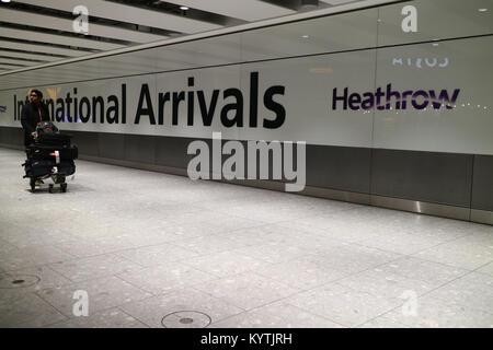 London, United Kingdom - 12/19/2017: London Heathrow's Terminal 5 International arrivals with a man arriving. - Stock Photo