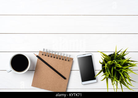 Smartphone, cup of coffee, notbook, and green plant on white wooden table - Stock Photo