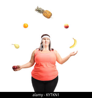 Overweight woman juggling with fruit isolated on white background - Stock Photo