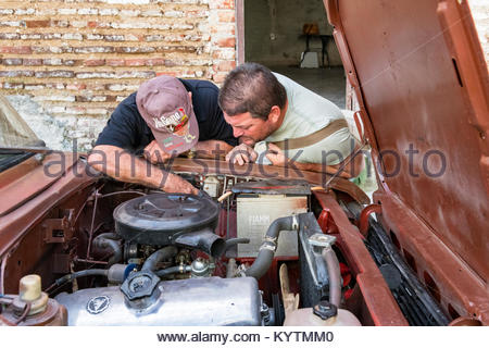 Two Cuban men repairing a car in the city street. It is a common practice to see Cuban doing their own repairs instead - Stock Photo