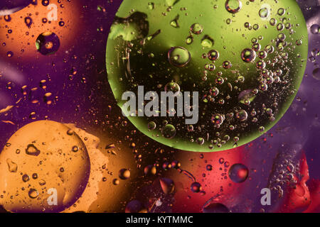 Unusual colorful background with oil drop circles and air bubbles that reflect yellow, orange, purple, green and - Stock Photo