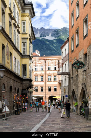 Street of the Old Town of Innsbruck Austria in sunny summer day. In the background above roofs of the houses, green - Stock Photo